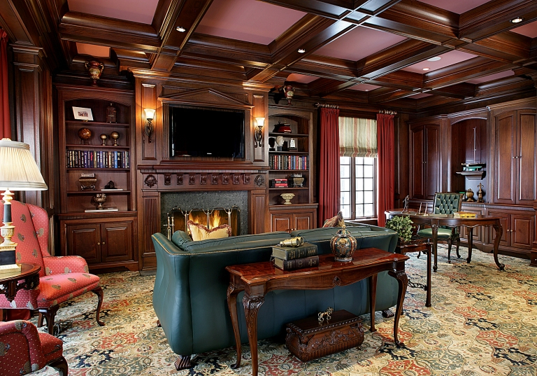Dark green decor adds a luxurious touch to rich wood features in this sitting room from Peter Salerno Inc.