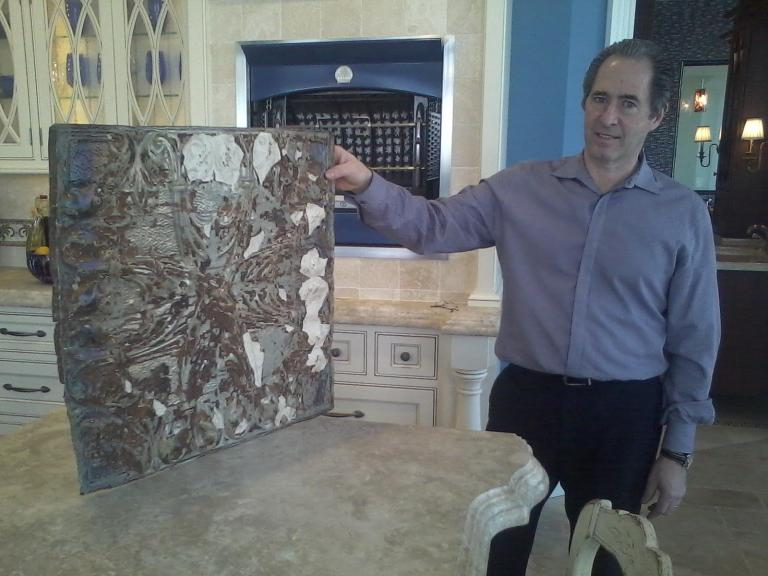 Peter Salerno, with a piece of reclaimed tin in his showroom...