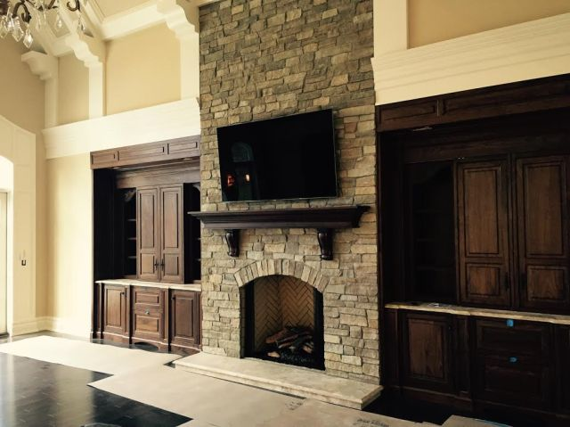 A beautiful stone fireplace and custom cabinetry from Peter Salerno Inc.