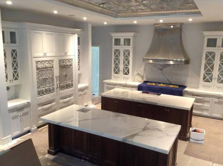 This Jupiter, FL kitchen utilizes glass cabinets to open the design space.
