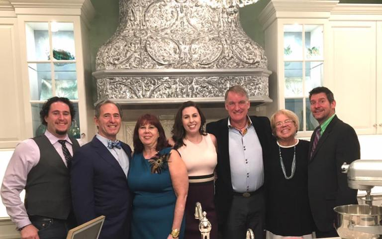 The 2017 Designer ShowHouse of NJ team, in front of a gorgeous reclaimed tin custom range hood.