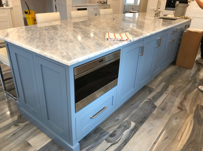 This blue kitchen island pops in a neutral color kitchen design. (Peter Salerno Inc.)